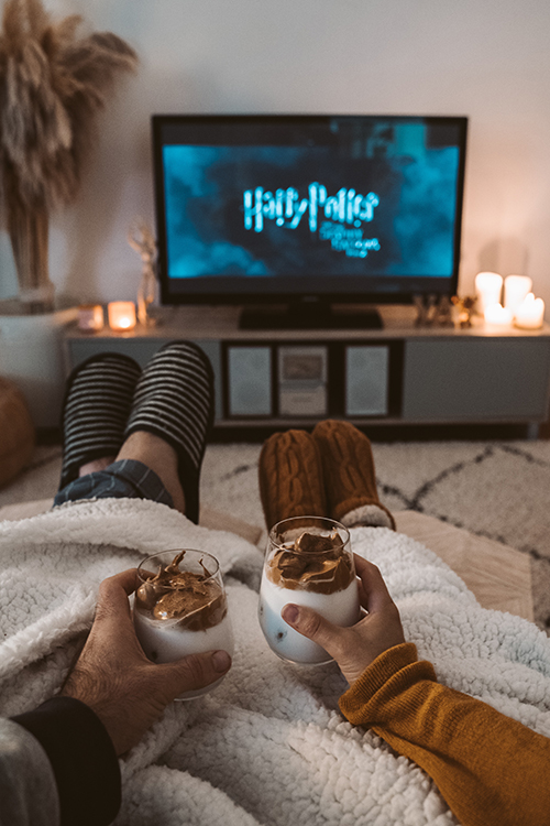 Couple with feet propped up and hot chocolate drinks toasting in front of TV.